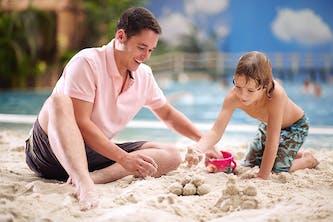 Vater und Sohn im Tropical Island sitzend im Sand und formen Kugeln und bauen eine kleine Sandburg - direkt am Wasser und mit Palmen im Hintergrund - der Junge hat noch nasse Haare nd kommt wahrscheinlich frisch aus dem Wasser