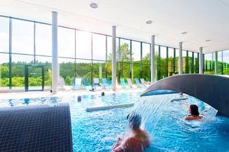 Schwimmbecken im Wellness Bereich vom Hotel mit Therme - Menschen erholen sich im Wasser mit einem kleinen Wasserfall der die Rückmuskulatur ein wenig massiert und lockert - im Hintergrund sind große Fenster die den Blick auf den Wald und die Hügel freigibt