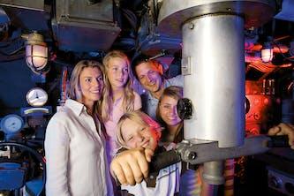 Familie - Eltern mit 3 Kindern in den Bavaria Filmstudios und sehen sich eine Attraktion - sie lächeln in die Kamera und sehen zufrieden und ausgeglichen aus
