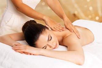 Wellness Behandlung Rückenmassage in einem Wellnessurlaub - die Frau die massiert wird sieht tiefenentspannt aus und sehr friedlich - die Masseurin macht Ihre Anwendung vorbildlich für Ihre Beauty Kundin