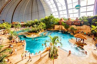 Tropical Island Resort nähe Berlin von innen fotografiert - tropische und karibische Atmosphäre mit Palmen, Strandhäusern wie in Hawaii und Wellengang im Poolbereich mit kleinem Wasserfall