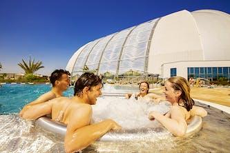 Pool und Whirlpool vor der Therme Erding - gigantisch und einladend im Hintergrund - im Whirlpool sitzen 4 Personen 2 junge Frauen und Männer die freudestrahlend miteinander lachen und die Therme Erding in vollen zügen und entspannt genießen