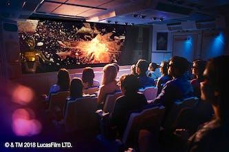 3D Kino in Disney Land Paris auf der Leinwand wird Krieg der Sterne mit einer Weltraumschlacht gespielt und die Zuschauer sitzen auf ihren Plätzen und haben 3D Brillen auf und der Raum und die Wände sehen aus wie ein Raumschiff von Innen wie bei Star Wars