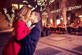 Ein verliebtes Paar küsst sich und er hebt sie leicht hoch und hat seine Arme um sie gelegt - sie wirken sehr glücklich und im Hintergrund sind Stühle von einem Cafe zu sehen und Lichterketten hüllen den Fußweg in ein orangenes und romantisches Licht