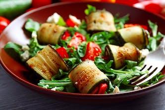 Ein köstlich angerichtetr Teller mit vegetarischem Essen für das Wellness Wochenende - Zuchini Tomaten Rucola und Parmesan Antipasti Gericht und gesund für die schlanke Linie