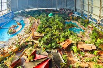 Tropical Island Innenbereich von oben fotografiert - man sieht fast alle Bereiche, Palmen die Zelte und Häuser - erst von oben wird sichtbar wie klein die Menschen im Gegensatz zu dem riesigen Tropical Island Komplex - oder genauer der Kuppel sind. Eine traumhafte Urlaubswelt für die ganze Familie