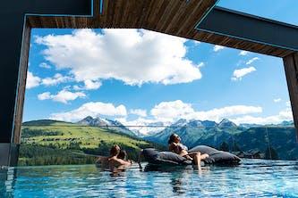 Überdachter Outdoor Swimmingpool mit 3 entspannten Personen darin - eine sitzt auf einem schwimmenden Kissen und genießt die Sonne - die anderen beiden Personen stehen zusammen im Wasser und sehen die großen gut sichtbaren Berge und Wälder - der himmel strahlt blau mit wenigen Wolken