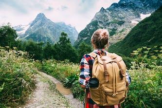 Erholung in der Natur oder den Bergen beginnt bereits mit einem kleinen Spaziergang auf den Wanderwegen oder Bergpfaden - auf dem Bild sieht man eine junge Frau mit Rucksack Sie geht einen Wanderweg in ihrem Urlaub und man sieht Berge Wälder und einen schönen blauen Himmel