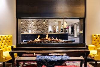 Feuer in einem durchsichtigen Kamin in der Nähe von der Rezeption im Hotel – zwei gelbe Sessel und eine Holzbank mit einem kleinen blauen Fellbezug liegt darauf – der bunte Teppich rundet die Atmosphäre im Hotel ab – so lässt es sich um Urlaub oder auf Kurzreisen gut gehen