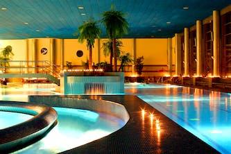 Therme im Wellness Hotel mit Palmen orangenen Licht und schimmerndes klares Wasser - Das Thermenbad bietet viel Platz zum Schwimmen liegen und erholen