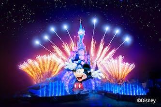 Disney Schloss mit Mickey Mouse in Comicform und Feuerwerkraketen steigen in die Luft und hüllen das Disneyland Märchenschloss in einen Schein aus unterschiedlichen Farben wie Blau und Orange und am Himmel sind die Sterne zu sehen