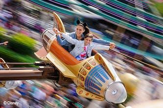 Disneyland Paris Mutter und Tocher in einer der Fahrgeschäfte und Fahren beziehungsweise fliegen mit einer Rakete im Kreis - der Hintergrund ist verschwommen, durch die schnelle Drehung und Bewegung - die Mutter hat die Mini Mouse Ohren auf dem Kopf