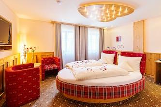Bett in Herzform in einem romantischen Zimmer in einem Kuschelhotel - optimal für verliebte und liebende - mit Rosenblättern auf dem Bett wirkt es sehr einladend für intime Stunden zu zweit - die Lampe an der Decke ist auch in Herzform - das gesamte Bild wirkt sehr romantisch und stimmig