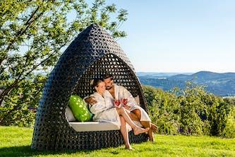 Verliebtes Pärchen sitzt entspannt in einer Sonneninsel - Liegeinsel im Bademantel und sehen glücklich aus - im Hintergrund sind Wälder Hügel und kleinere Berge zu sehen - der Himmel strahl blau und wolkenlos - so möchte man seinen romatischen Kurzurlaub verbringen